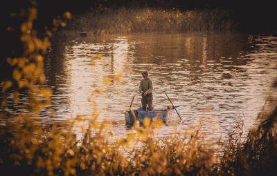 A man fishing from a boat on a lake in the autumn.