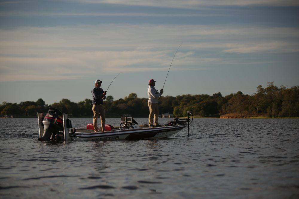People fishing from a boat on a lake daytime.
