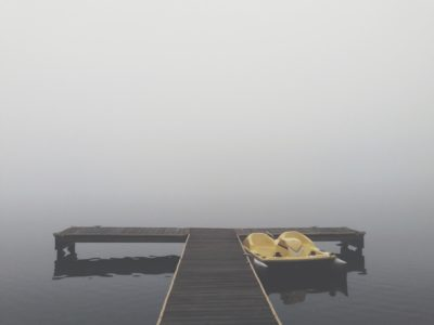 A dock by the lake in the fog.