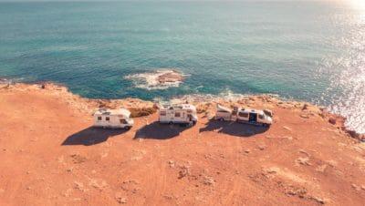 Three white RVs by the ocean.