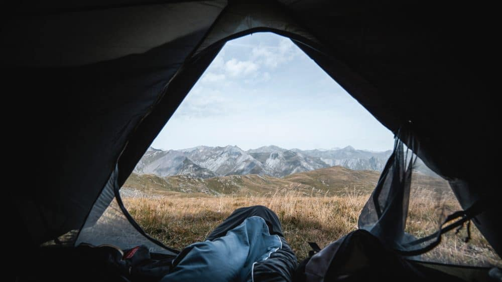 A sleeping bag in a tent with a mountain view.