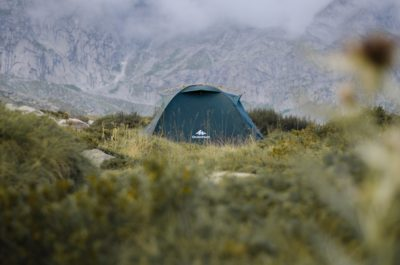 A green tent in the mountains.