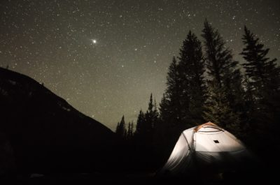 A tent under the stars at night.