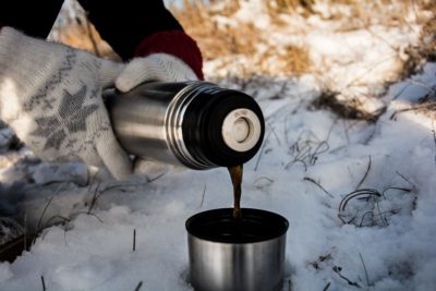 A person pouring coffee into a mug in the snow.