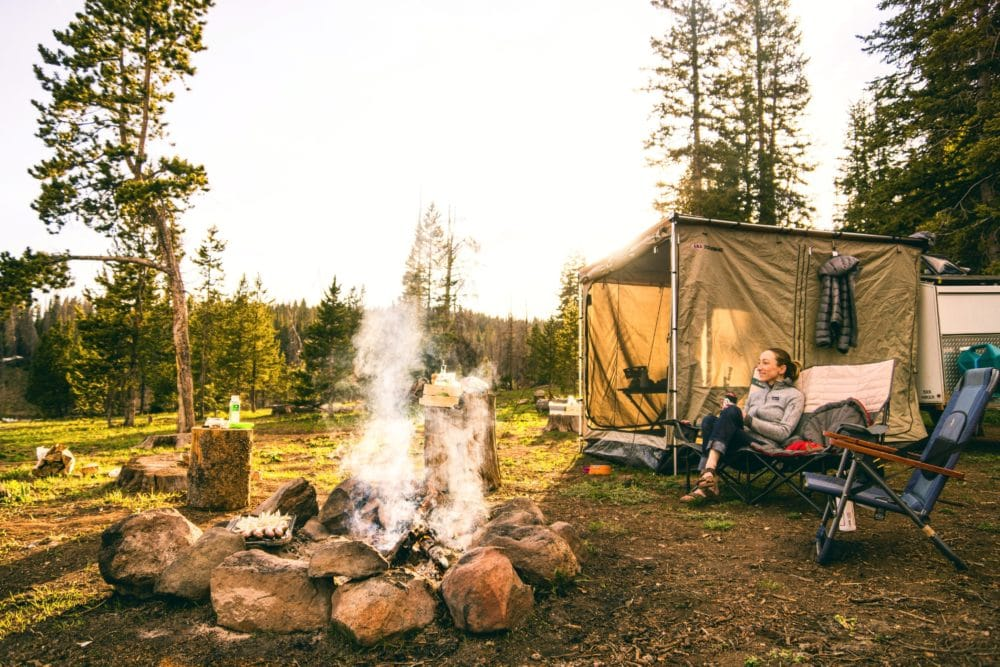 A woman sitting on a chair at a campsite outside.