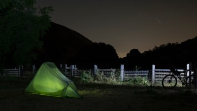 A green tent in a field at night.