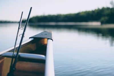 The tip of a boat and some fishing rods on the lake.