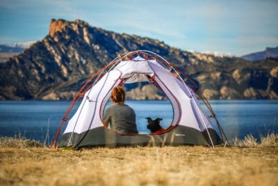 A girl in a tent with her dog by the water.