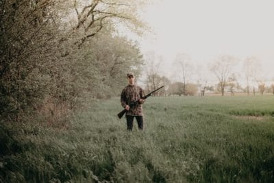 A young boy holding a hunting shotgun in a field.