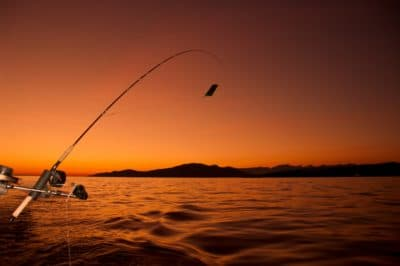 A person fishing during sunset.