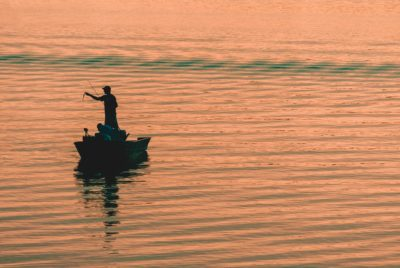 A person fishing from a boat during sunset.