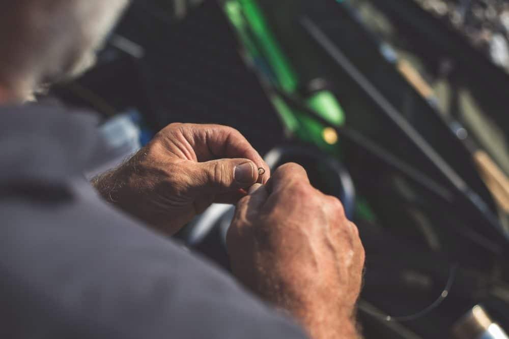 A man tying a fishing knot.