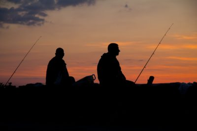 Two people fishing during sunset.