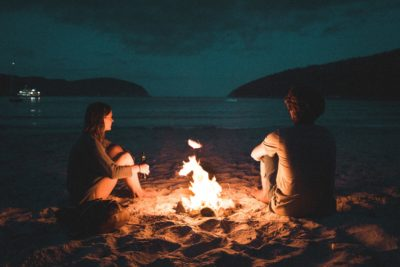 People sitting around a campfire on the beach.