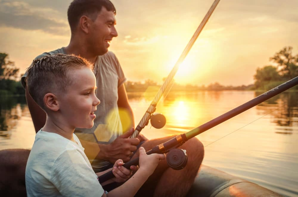 A man and his son fishing sunset.