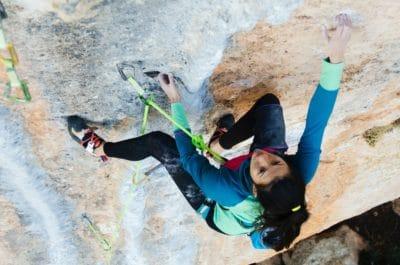 A woman climbing on a rock.