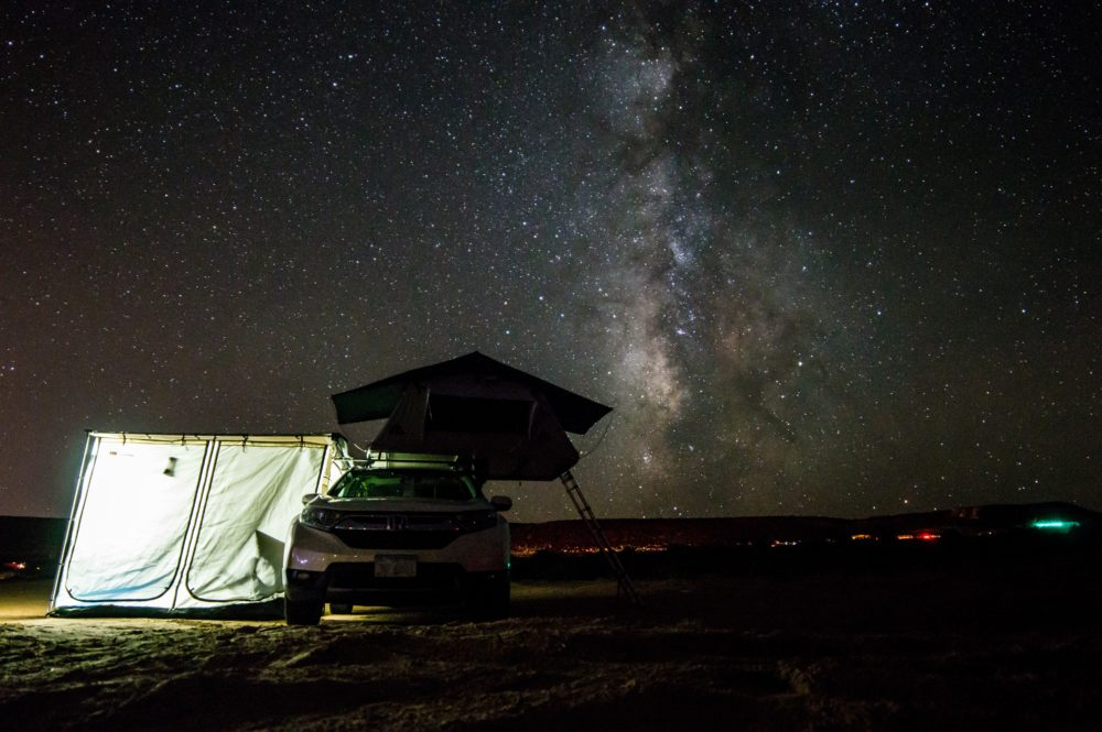 An SUV with a tent attached under the stars.