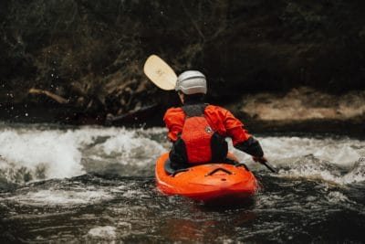 A man on an orange kayak on a river.