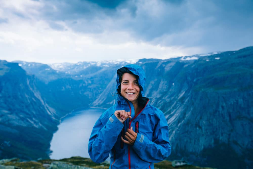 A girl in the mountains with a rain jacket.