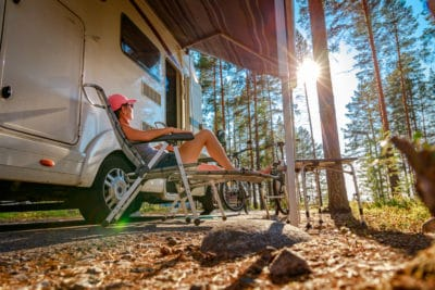 A woman camping by an RV.