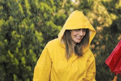 A woman wearing a yellow rain jacket in the rain.