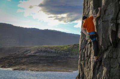 A man climbing by a lake.