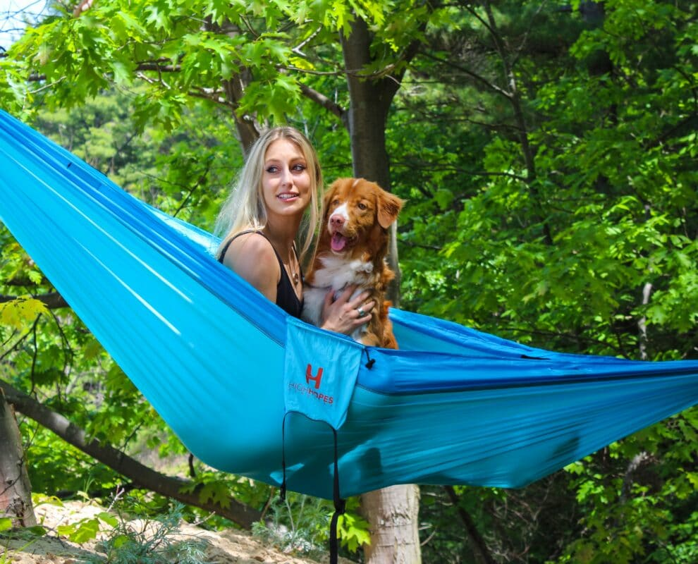 A girl camping in a hammock with her dog.