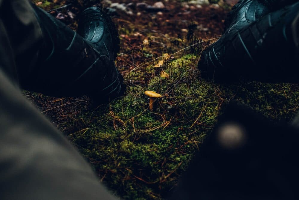 A hunter wearing hunting boots outdoors.