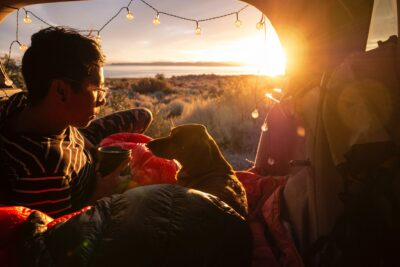A guy in his tent with his dog during sunrise.