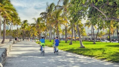 People riding bikes on a sidewalk in Miami.