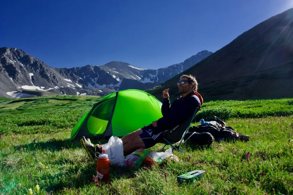 A man camping in the mountains.