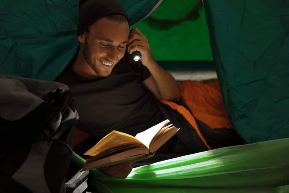 A man reading a book in a tent.