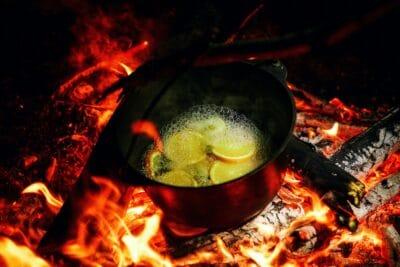 A pot boiling over a campfire.