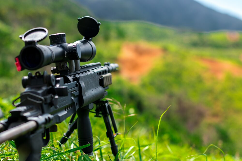A rifle with a scope on it outdoors.
