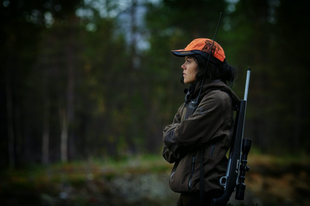 A girl hunting with a rile and scope.