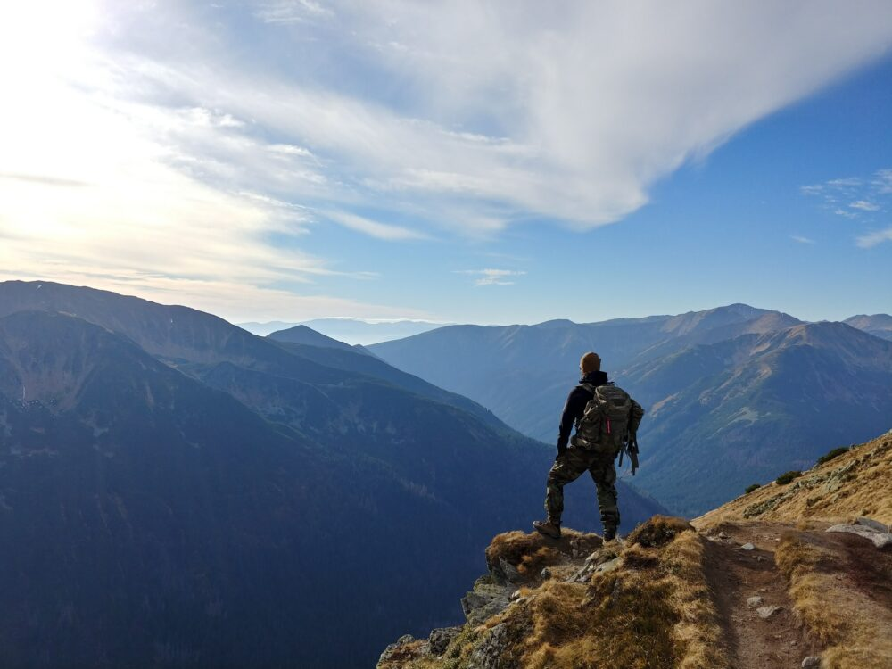 A man with a bug out bag standing on a mountain daytime.