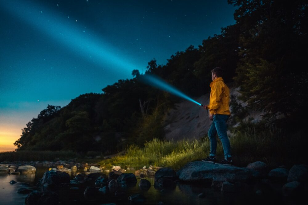A man holding a flashlight and looking at the sky.