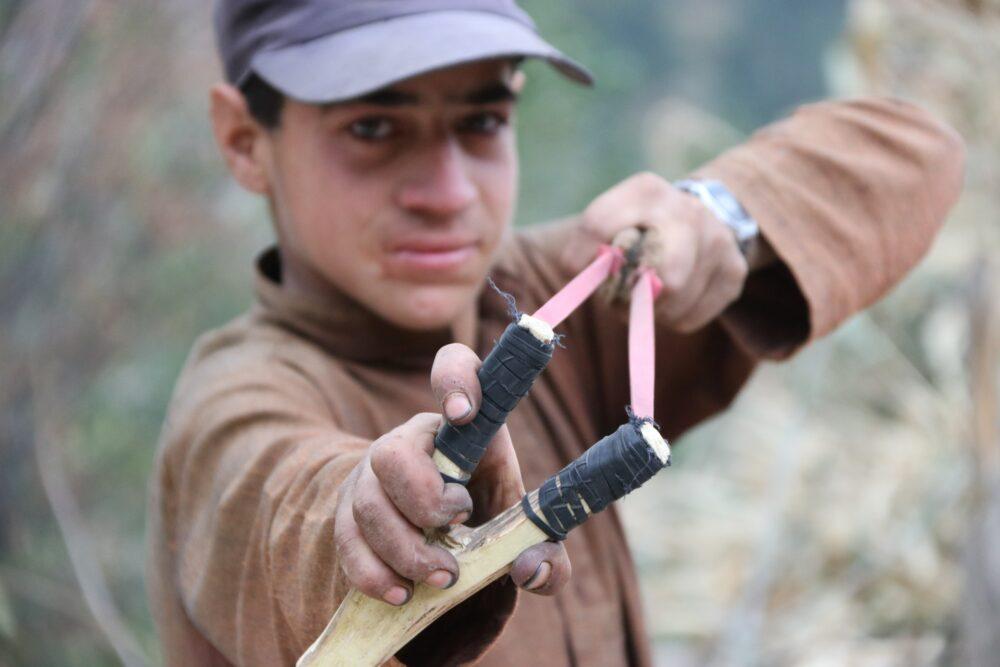 A boy holding a slingshot.