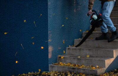A person using a leaf blower on some stairs.