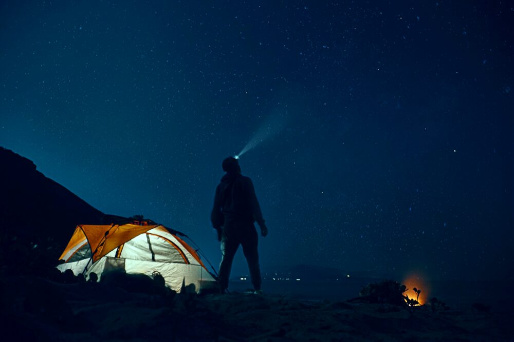 A man wearing a headlamp and standing next to a tent.