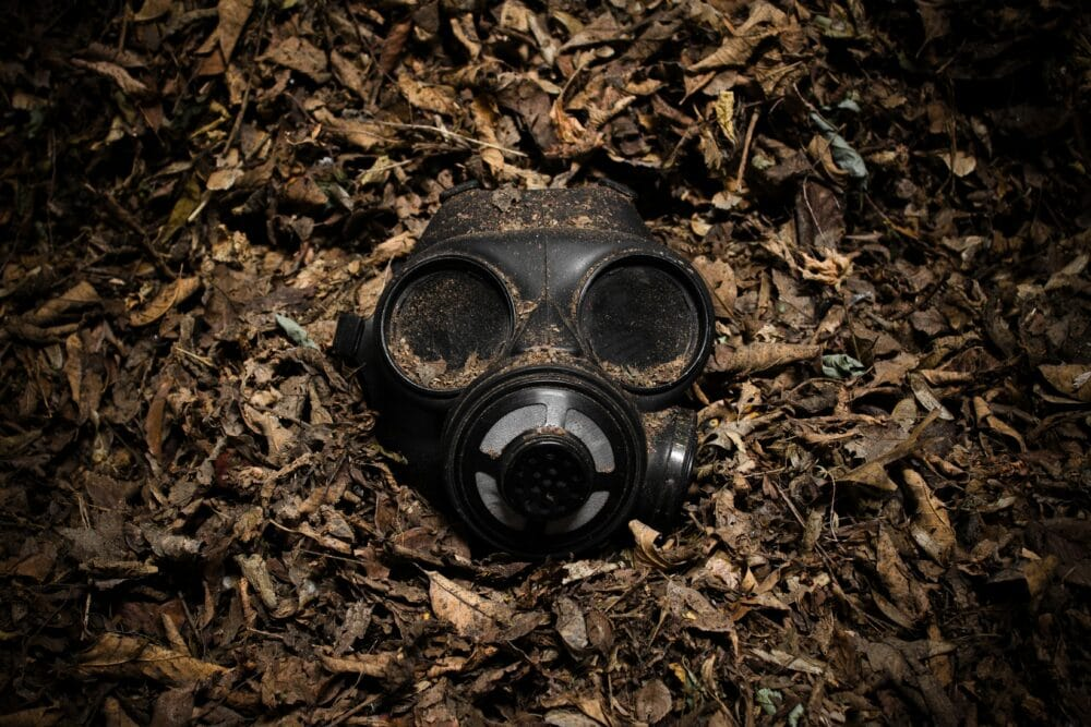 A gas mask in a pile of dead leaves.