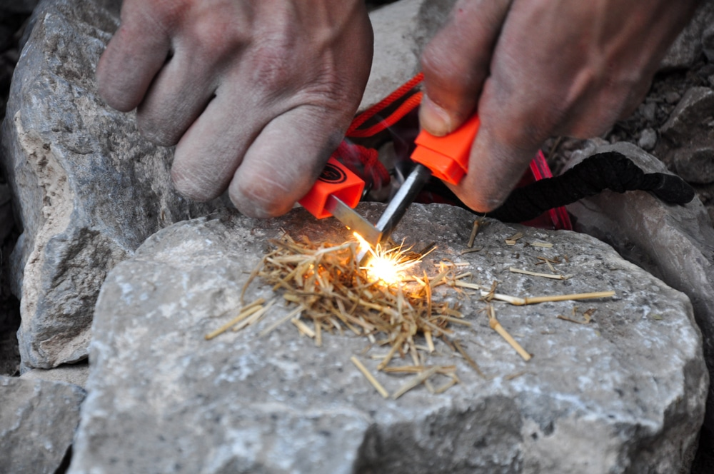 A lighter and hay being used to start a fire.