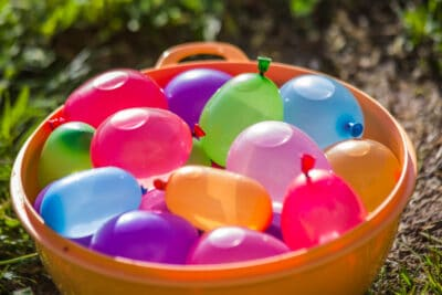 Colorful water balloons in an orange bucket.