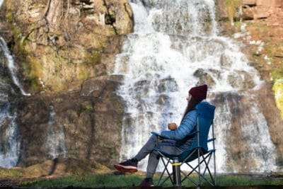 Woman drink tea or coffee from a thermos, sitting on camp chair near a waterfall.