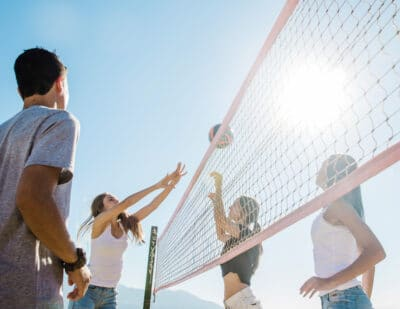 Group of young Friends Playing Volleyball outdoors.