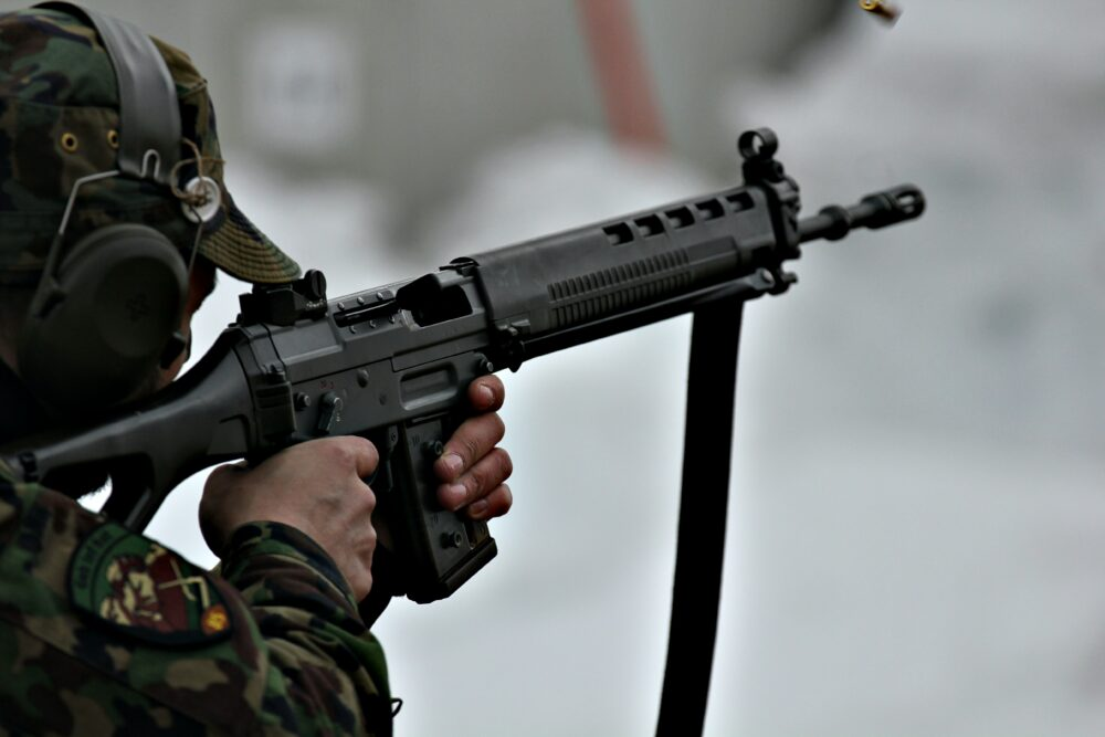 A person holding a black assault rifle.