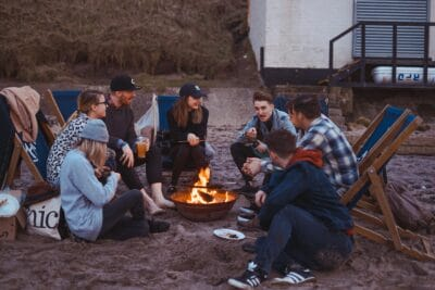 A group of people sitting in front of fire.