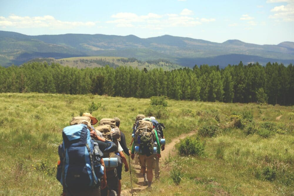 People with backpacks on a hike.