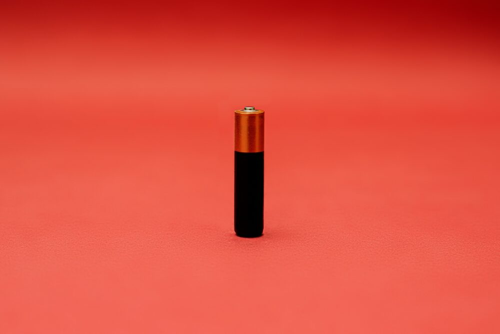 A battery on an orange background.