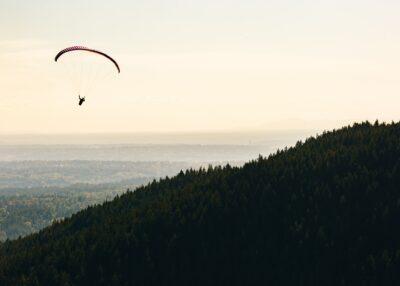 A person paragliding off a mountain